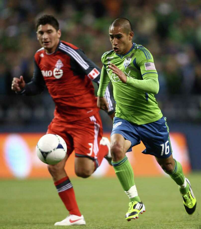 Sounders player David Estrada runs for the ball against Toronto FC player Miguel Aceval dirng the Seattle Sounders MLS season opener against Toronto FC on Saturday, March 17, 2012 at CenturyLink Field in Seattle. Photo: JOSHUA TRUJILLO / SEATTLEPI.COM