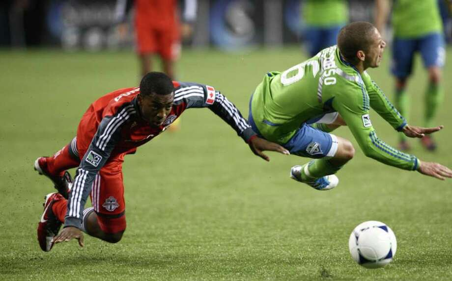 Toronto FC player Aaron Maund and Seattle Sounders player Osvaldo Alonso collide in the second half of the MLS season opener against Toronto FC on Saturday, March 17, 2012 at CenturyLink Field in Seattle. Alonso was injured in the play. Photo: JOSHUA TRUJILLO / SEATTLEPI.COM
