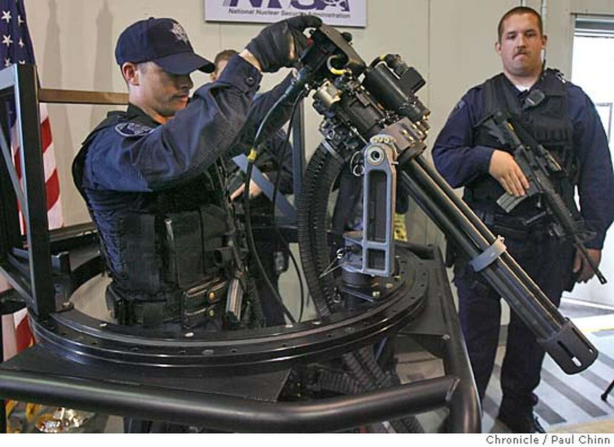 Lawrence Livermore police officer Andrew Graycar demonstrates how the new Dillon Aero gatling gun swivels as police officer Chris McKaskey (right) stands guard in Livermore, Calif. on 2/2/06. The state-of-the-art weapon, capable of firing up to 4,000 rounds per minute, will add to the arsenal already in place to protect the Lawrence Livermore National Laboratory. PAUL CHINN/The Chronicle