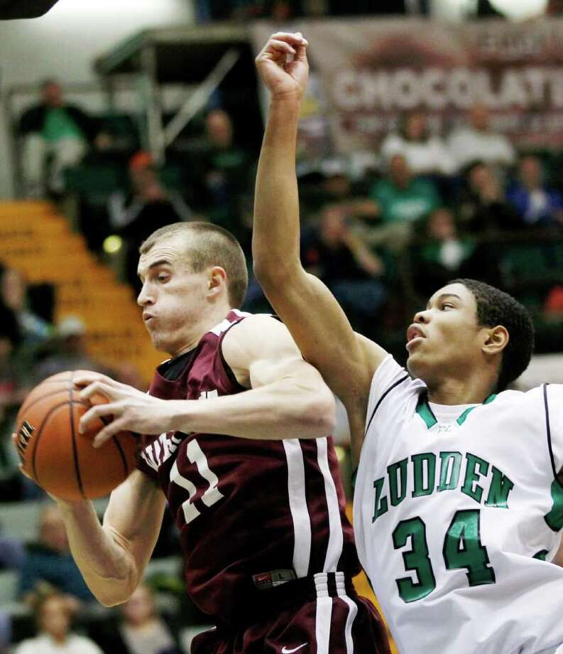 Watervliet's Griffin Kelly (11) grabs a rebound in front of Bishop Ludden's Daniel Kaigler (34) during a New York State Public High School Athletic Association boys' Class B championship basketball game in Glens Falls, N.Y., on Saturday, March 17, 2012. (AP Photo/Mike Groll) Photo: Mike Groll