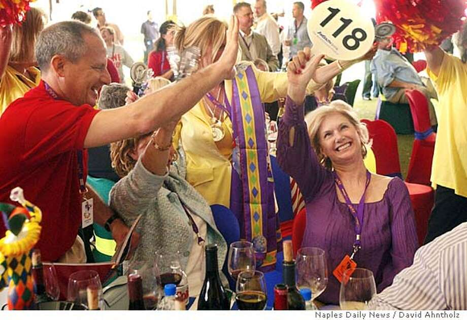 Wine festival trustee Shirlene Elkins, right, of celebrates her winning bid during the Winter Wine Festival auction at the Ritz-Carlton Golf Resort Saturday afternoon, January 28. Elkins won the bid on a 3 day, 4 night trip on Treasure Cay in the Bahamas packaged with wine, gourmet meals, and tennis instruction from Johan Kriek. Photo by David Ahntholz/ Daily News Fort Myers News Press OUT; ; No Mags Photo: David Ahntholz/Naples Daily News