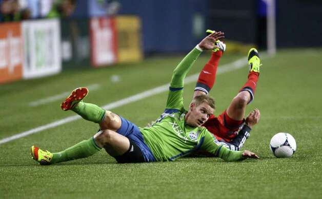 Sounders player Christian Sivebaek tangles with Toronto FC player Logan Emory during the second half. Photo: JOSHUA TRUJILLO / SEATTLEPI.COM