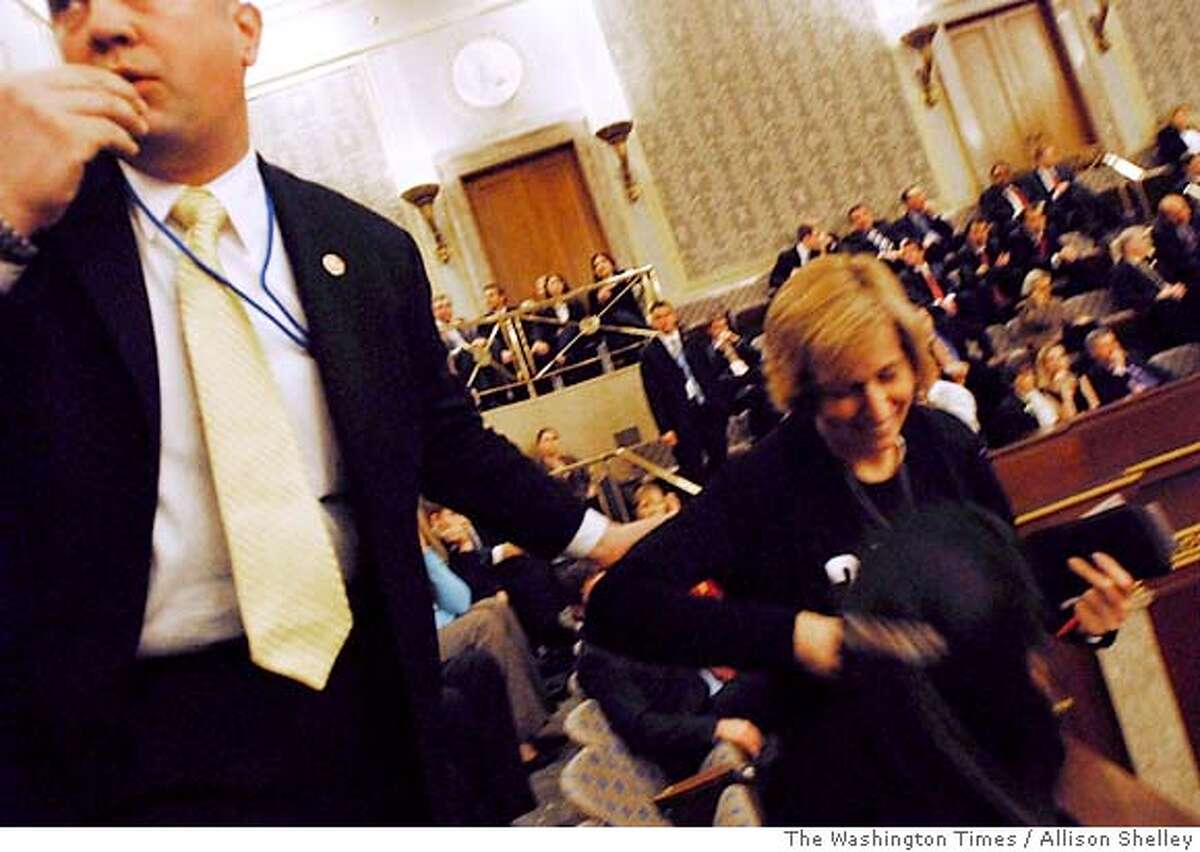 Security escorts Peace activist Cindy Sheehan from the U.S. House of Representatives before President Bush's State of the Union address on Capitol Hill, Tuesday, Jan. 31, 2006, in Washington. Sheehan, the mother of a fallen U.S. soldier in Iraq who reinvigorated the anti-war movement, was arrested and removed from the gallery, a police spokeswoman said. (AP Photo/The Washington Times, Allison Shelley) ** MAGS OUT, TV OUT, **