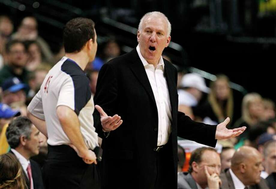 San Antonio Spurs head coach Gregg Popovich talks to referee Brian Forte (45) after a foul call against his team in the second half of an NBA basketball game against the Dallas Mavericks Saturday, March 17, 2012, in Dallas. The Mavericks won 106-99. (AP Photo/Tony Gutierrez) (AP)
