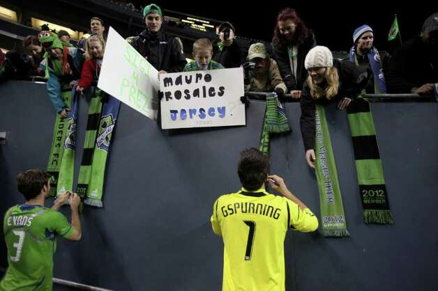 Sounders players Brad Evans, 3, and Michael Gspurning sign autographs after the win. Photo: JOSHUA TRUJILLO / SEATTLEPI.COM