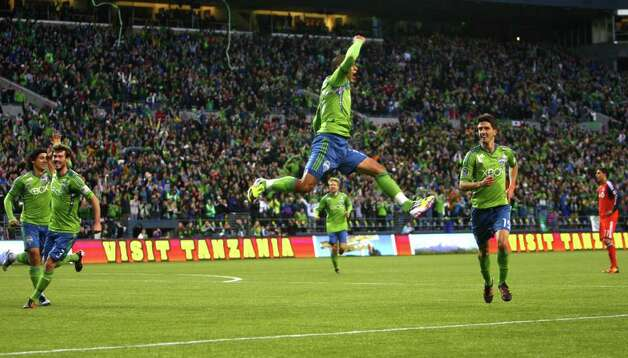 David Estrada, center, leaps as he celebrates with teammates Alvaro Fernandez (15) and Fredy Montero (17), left, after Estrada scored a first-half goal. Photo: JOSHUA TRUJILLO / SEATTLEPI.COM