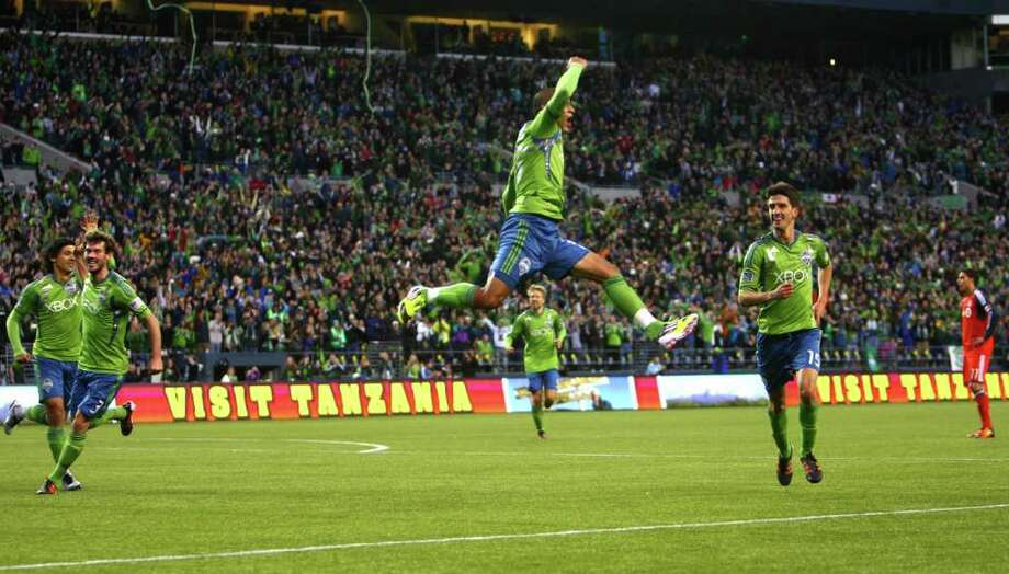 Seattle Sounders player David Estrada, center, leaps as he celebrates with teammates Alvaro Fernandez (15), and Fredy Montero (17), left, after Estrada scored a first half goal in the MLS season opener against Toronto FC on Saturday, March 17, 2012 at CenturyLink Field in Seattle. Photo: JOSHUA TRUJILLO / SEATTLEPI.COM