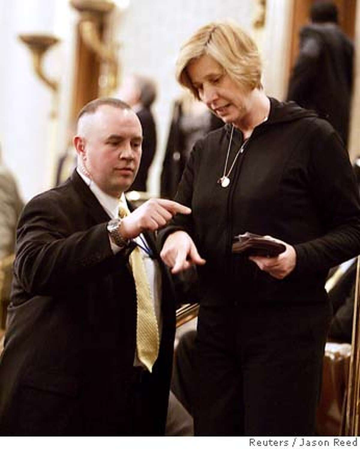 Anti-war protester Cindy Sheehan, whose son was killed serving as a U.S. serviceman in Iraq, talks with security personnel in the U.S. House of Representatives chamber after arriving for the State of the Union address by U.S. President George W. Bush on Capitol Hill in Washington January 31, 2006. Sheehan was escorted back out of the chamber a short time later and there were unconfirmed reports that she had been arrested. REUTERS/Jason Reed