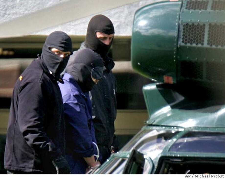 """An unidentified man, centre, believed to be a terror suspect, is led past a helicopter by masked police, at the German Federal Court in Karlsruhe, southern Germany, Wednesday, Sept.5, 2007. Authorities said Wednesday they had arrested three suspected Islamic terrorists from a group with """"profound hatred of U.S. citizens'' for plotting imminent, massive bomb attacks on U.S. facilities in Germany. (AP Photo/Michael Probst) Photo: MICHAEL PROBST"""