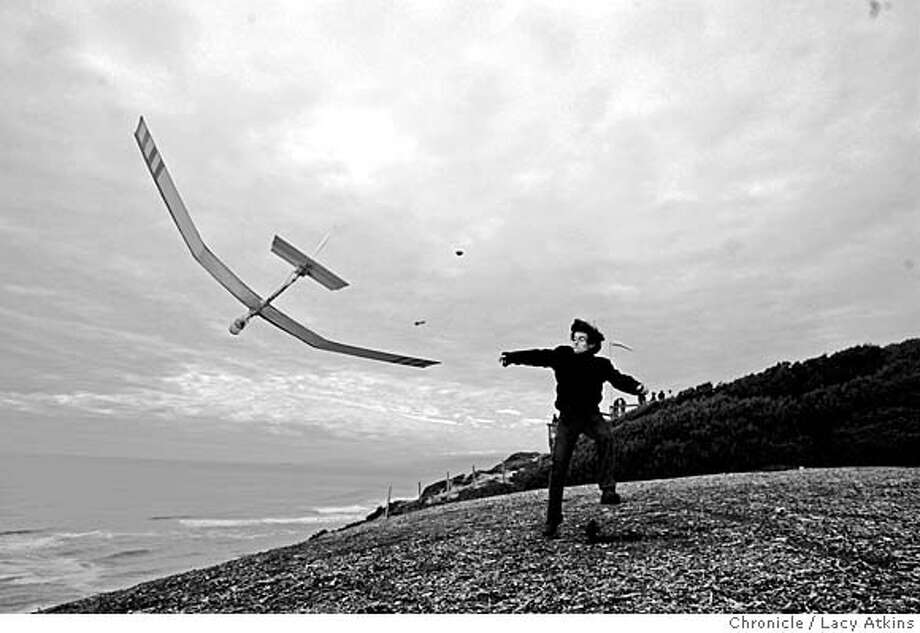Numo Fontes pass the time away Sunday Jan. 29, 2006 by throwing rocks at his friends glider at Fort Funston, in San Francisco. Both he and his friend Larry Carpenter are hang gliders passing the time as they wait to see in the wind kicks up for flying.  Photographer: Atkins, Lacy Photo: LACY ATKINS
