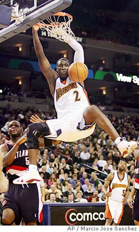 Golden State Warriors' Mickael Pietrus, of France, dunks past Portland Trail Blazers' Zach Randolph during the first half of an NBA basketball game Saturday, Jan. 28, 2006, in Oakland, Calif. (AP Photo/Marcio Jose Sanchez) EFE OUT Photo: MARCIO JOSE SANCHEZ