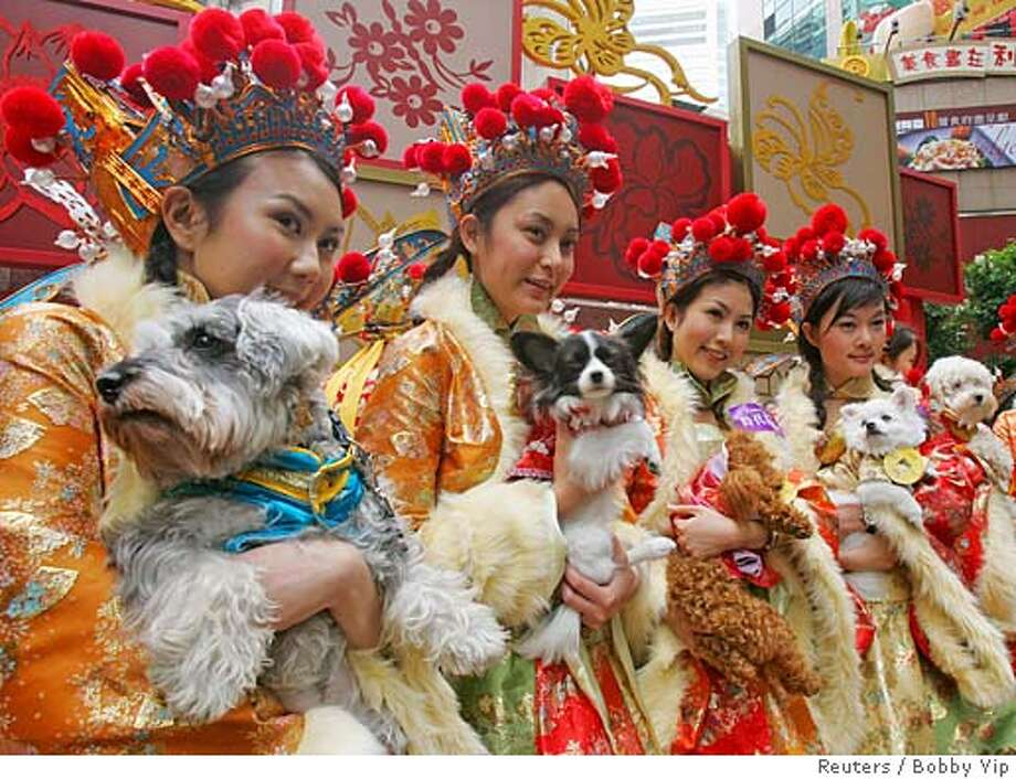 """Attendants dressed as """"Goddesses of Wealth"""" carry """"fortune puppies"""" as part of a promotion event outside a shopping mall in Hong Kong January 23, 2006. Retailers in the territory are arranging various kinds of cultural performances in a bid to boost sales before the Chinese Lunar New Year of the Dog which falls on January 29. REUTERS/Bobby Yip Ran on: 01-29-2006  Attendants dressed as goddesses of wealth carry &quo;fortune puppies&quo; as part of Year of the Dog promotions outside a shopping mall in Hong Kong. Photo: BOBBY YIP"""