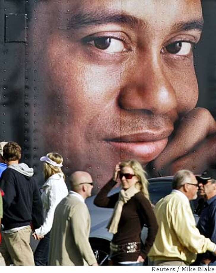A picture of golfer Tiger Woods on the side of a semi-tractor trailer looks out over the crowd during third round play at the Buick Invitational golf tournament on the south course at Torrey Pines in San Diego, California January 28, 2006. Buick is one of Wood's many sponsors. REUTERS/Mike Blake 0 Photo: MIKE BLAKE