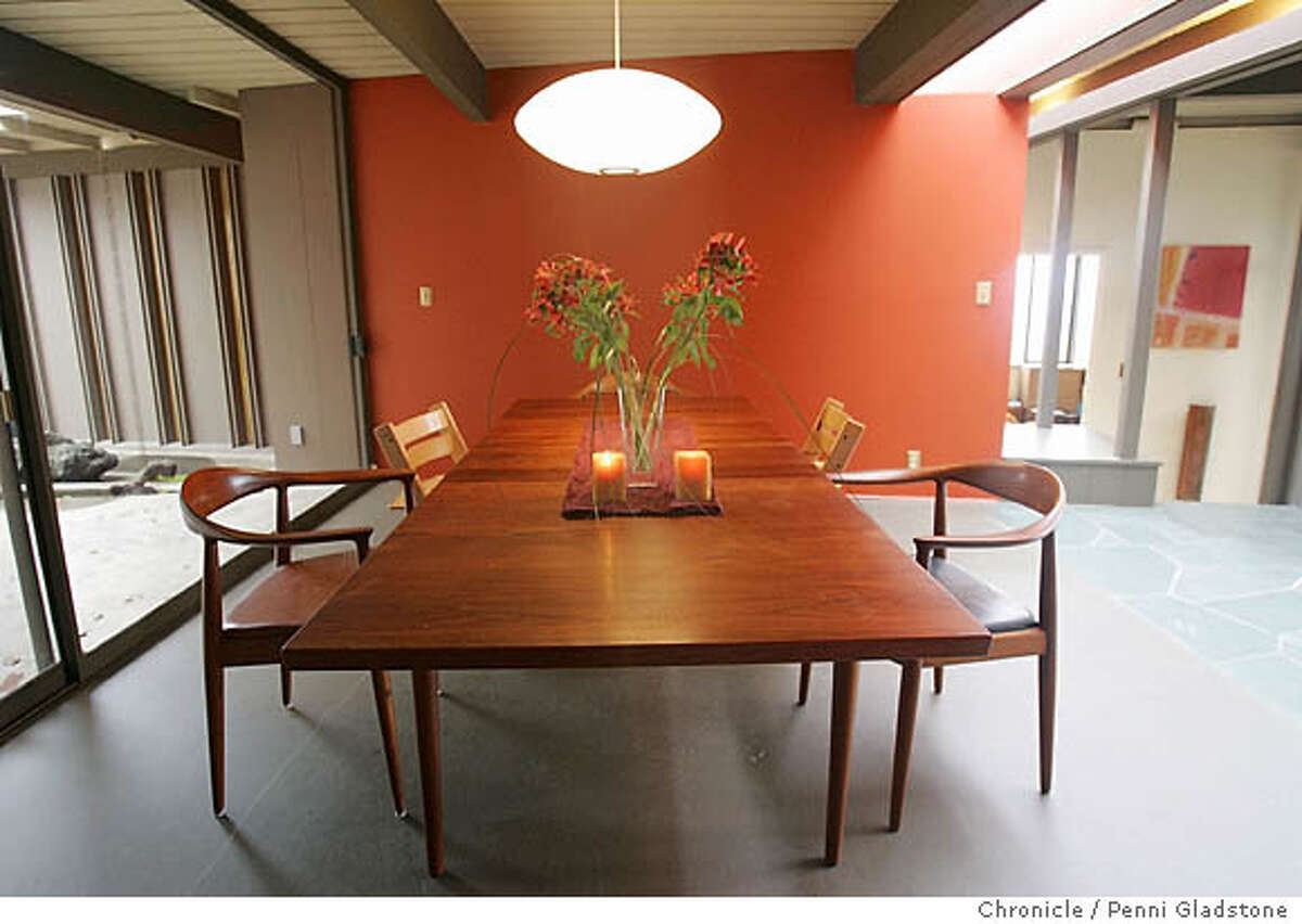 """Dinning room. We are running a story on the work of architect John Hans Ostwald. One house Ostwald designed is a 3020 Buena Vista Way in Berkeley. This is a """"two-part"""" house with a butterfly roofed section above and a flat-roofed section below, tied together by a """"breezeway,"""" with a glassed-in hall and dining room. The house has a characteristic prow-shaped deck off the living room and a dramatic photo could be had showing part of the butterfly roof leaping up and the see-throuhg living room. At one end of the living room is a triangular seat which continues on through the glass -- there's a mirror version of the seat outside. Photo by Penni Gladstone/The San Francisco Chronicle Photo taken on 1/3/06, in Berkeley, CA."""