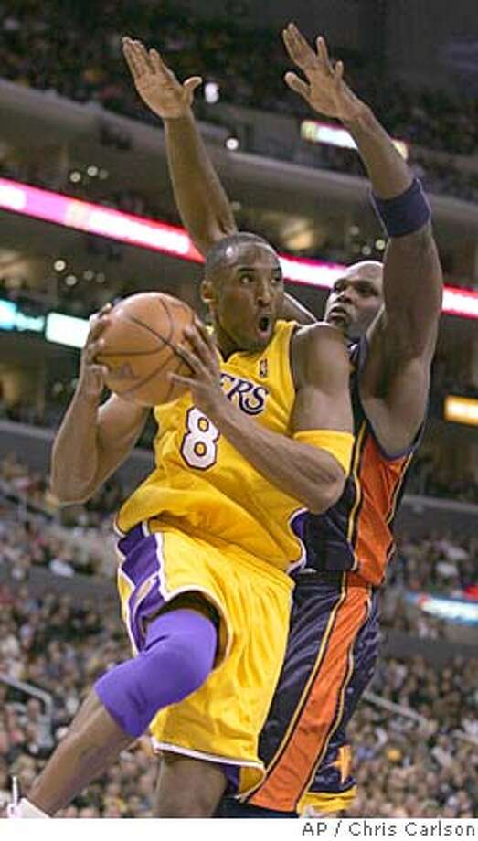 Los Angeles Lakers' Kobe Bryant goes to the basket past Golden State Warriors' Adonal Foyle during the first half of an NBA basketball game Friday, Jan. 27, 2006, in Los Angeles. (AP Photo/Chris Carlson) Photo: CHRIS CARLSON