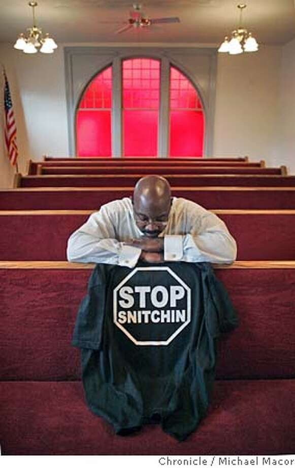 snitching_024_mac.jpg Rev. Robinson inside his church along Martin Luther King Blvd. in Oakland, with the tee shirt he wore as he delivered a sermon recently. The shirt was purchased right across the street from his church. Right or wrong, the code of the street in the poor, largely black neighborhoods in of the Bay Area is never, ever cooperate with police. To do so, the idea goes, means risking the wrath of criminals who might be neighbors or even relatives. It�s an ethos that cuts across generations, even as some who embrace it complain that police do little about the crime ravaging their neighborhoods. And it�s a mindset that is moving from the streets to the mainstream, carried by rap tunes denouncing rats and T-shirts declaring �Stop Snitchin�� and �Snitches Get Stitches.� The T-shirts especially have proven popular in Oakland and elsewhere, prompting a debate within the communities where they�re worn and frustrating police who say it�s one more hurdle to effective policing in the communities that need it most. �The young men wearing the shirts are putting out fear,� said the Rev. Curtis Robinson, senior pastor of Rising Star Missionary Baptist Church in Oakland. Robinson wore a Stop Snitchin' shirt in November as part of a sermon which was critical of the Stop Snitchin' ethos. �If you see somebody wearing a shirt, you know they are affiliated with a group of people who are not committed to building up the neighborhood, but instead are trying to tear it down,� Robinson said  Such arguments don�t carry much weight with many residents of inner-city neighborhoods, who argue the T-shirts � bearing slogans such as �Ditches are for snitches� Event in Oakland, Ca on 1/13/06. Photo by: Michael Macor / San Francisco Chronicle Mandatory Credit for Photographer and San Francisco Chronicle/ - Magazine Out Photo: Michael Macor