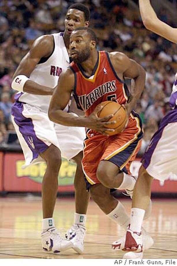 Golden State Warriors guard Baron Davis (5) drives past Toronto Raptors forward Chris Bosh during fourth quarter NBA action in Toronto, Canada, on Friday December 16, 2005. Davis had 20 points and 11 assists in the Warriors' 108-98 win. (AP Photo/Frank Gunn) Ran on: 12-17-2005  Baron Davis drives past the Raptors' Chris Bosh as the Warriors notched their sixth road win. Ran on: 12-17-2005 Ran on: 12-17-2005  Baron Davis drives past the Raptors' Chris Bosh as the Warriors notched their sixth road win. Ran on: 01-27-2006 Photo: FRANK GUNN