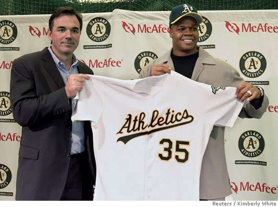 Frank Thomas (R) and Oakland Athletics general manager Billy Beane hold up an Athletics jersey during a news conference in Oakland, California January 26, 2006. Twice American League MVP Thomas has agreed to a one-year deal with the Oakland Athletics. REUTERS/Kimberly White 0 Photo: KIMBERLY WHITE