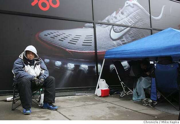 "Wilson Woo, 29, of San Francisco has been waiting since Wednesday for his new set of Jordans to add to his collection of 200 plus pairs of collectors shoes he already has at home. Woo said he took a week off from the shoe store he works at to wait in front of the Union Square store. Nike shoe collectors wait outside San Francisco's Nike Town store, some as long as a week, for a the chance to spend $300 for a set of limited edition Air Jordans released under the name ""Defining Moments."" san francisco on 1/27/06. Mike Kepka / The Chronicle Photo: Mike Kepka"