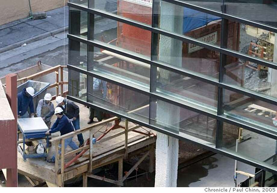 Construction workers (lower left) remove material beneath newly installed glass panels. Several large glass panels have been attached to the Mission St. facade of the Bloomingdale's project on 2/18/05 in San Francisco, CA.  PAUL CHINN/The Chronicle Photo: PAUL CHINN