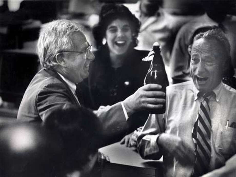 Celebrating his Pulitzer Prize in 1990, Allan Temko hoists a bottle of champagne in The Chronicle's newsroom with his fellow staffers Dawn Garcia and David Perlman. Chronicle file photo, 1990