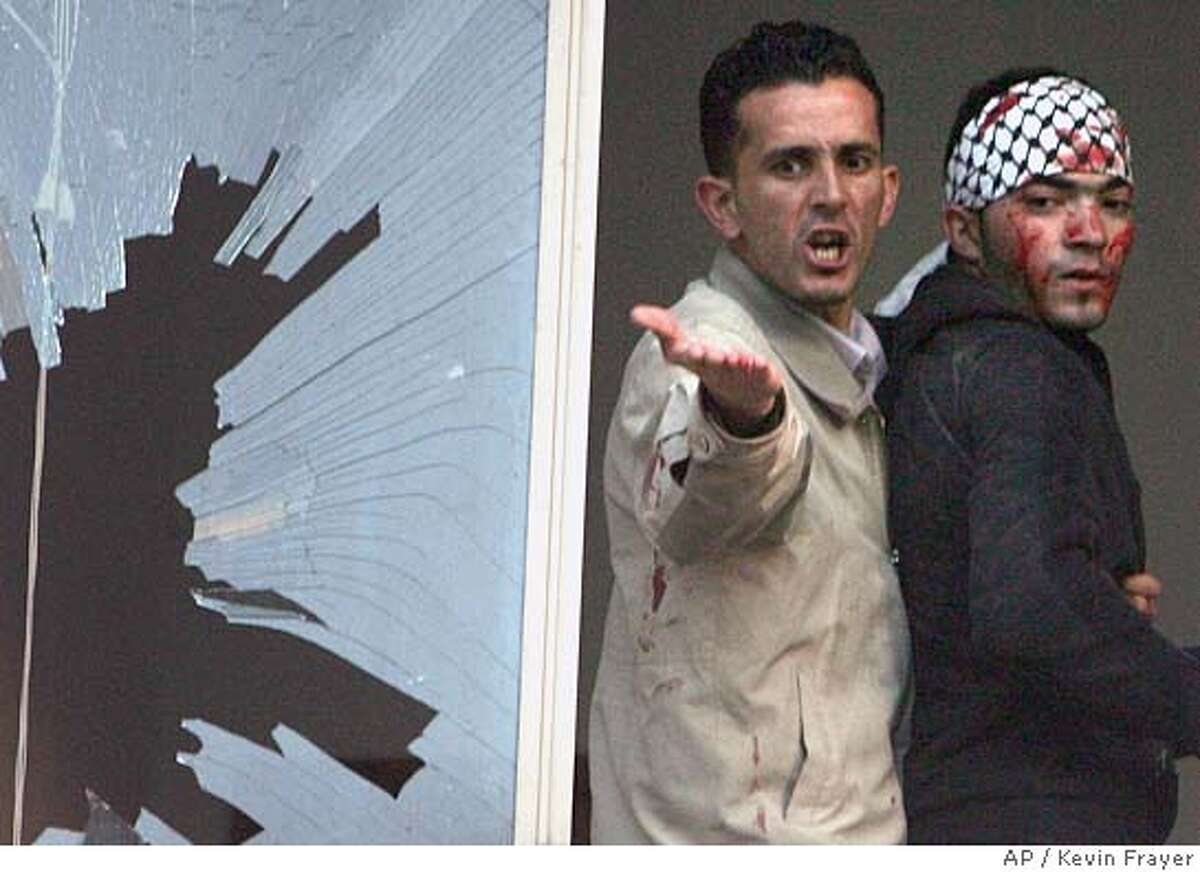 ** ALTERNATIVE CROP OF JRL141 ** A Palestinian pleads to the crowd to stop throwing stones as he helps an injured Fatah party supporter who was hit by a stone inside the Palestinian parliament building in the West Bank town of Ramallah Thursday Jan. 26, 2006. Hamas supporters briefly raised their flag over the Palestinian parliament and rushed into the building, amid clashes with Fatah loyalists. The two camps threw stones at each other, breaking windows in the building, as Fatah supporters briefly tried to lower the green Hamas banners. It was the first confrontation between Hamas and Fatah since the Islamic militant group won parliament elections on Wednesday. (AP Photo/Kevin Frayer) Ran on: 01-27-2006 A Palestinian pleads with a crowd to stop throwing stones, which injured a man, right, and broke a Parliament building window, left.