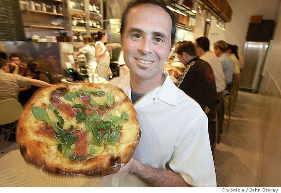 D29Delfina_Pizzeria_jrs_0334.jpg  Chef owner Craig Stoll holds up a pizza with potatos, arugula and prosciutto.Restaurant review of Pizzeria Delfina in San Francisco. John Storey San Francisco Event on 10/5/05 MANDATORY CREDIT FOR PHOTOG AND SF CHRONICLE/ -MAGS OUT Photo: John Storey