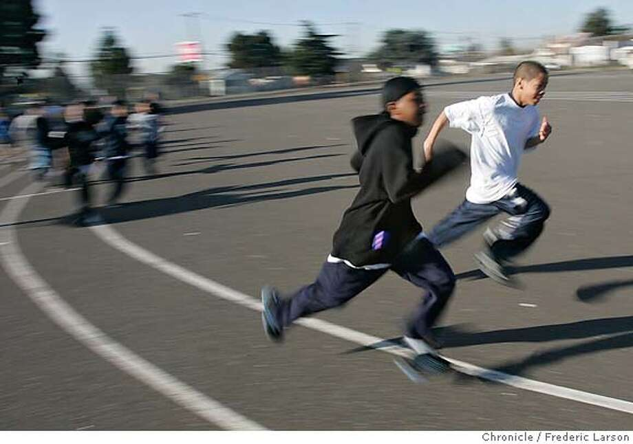 PHYS_ED_0139_fl.jpg Seventh graders race around the track during PE. At Frick Middle School, the physical education class looks a lot like bootcamp, with students standing in straight lines in their blue-and-white uniforms. PE teacher Kermit Bayliss walks through the rows with his bullhorn. As he calls out excercises, the students immediately preform them from memory while counting in sync. Students who don't participate get gloves and garbage bags and spend the 55 minute classes cleaning the school yard. The approach has allowed Frick Middle School to defy the odds by ranking near the top in the state's annual fitness test. Kids from low-income neighborhoods and minority kids have ranked lower in tests of fitnness and are at higher risk for obesity and illnesses related to poor fitness, according to studies. While about one-third of California seventh graders have an unhealthy percentage of body fat, only about one in ten students at Frick are considered unhealthy.  1/9/06 Oakland CA Frederic Larson San Francisco Chronicle Photo: Frederic Larson