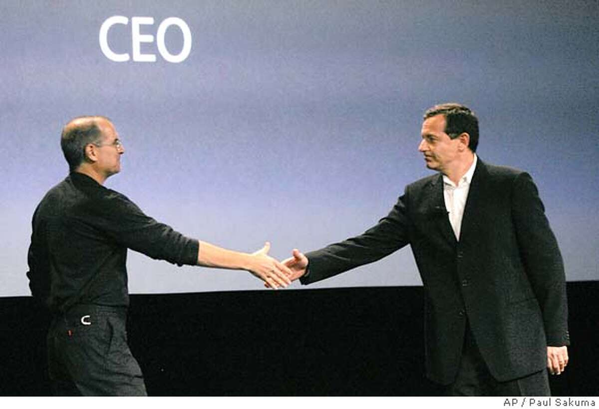 """**FILE**Apple Computer Inc. CEO Steve Jobs, left, shake hands with Disney CEO Robert Iger, right, during an unveiling in a San Jose, Calif. file photo from Oct. 12, 2005, of a new iPod with video capability. The Walt Disney Co. is in serious talks to buy Pixar Animation Studios Inc., the maker of the hit movies """"Toy Story"""" and """"Finding Nemo"""" among others, following months of exploring how to continue their profitable film distribution partnership, The Wall Street Journal reported Thursday. Jobs is also CEO at Pixar and is the largest shareholder in Pixar. (AP Photo/Paul Sakuma, File)"""