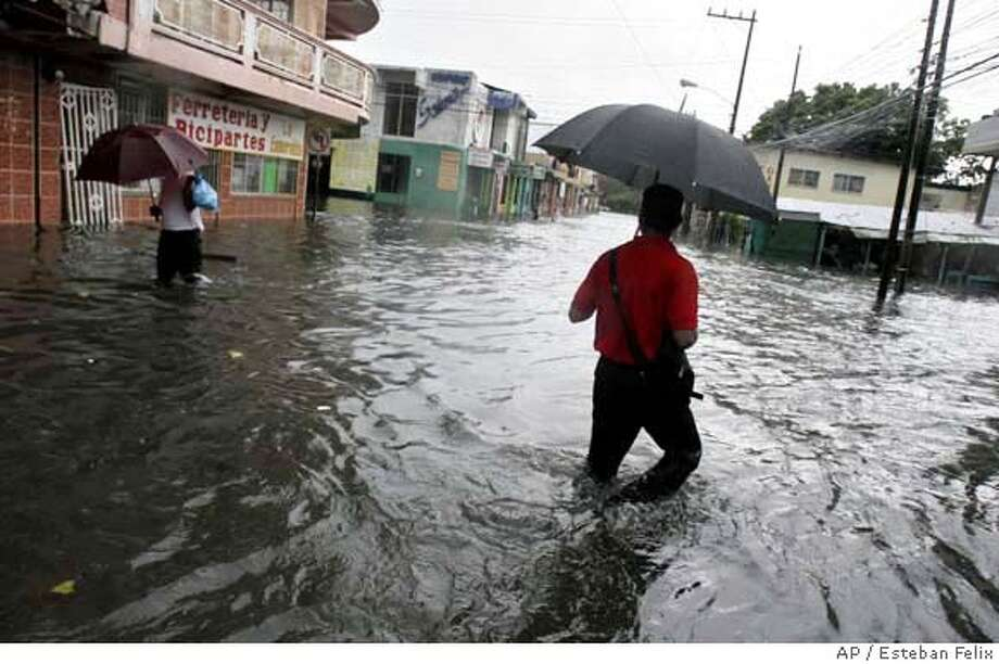 Residents walk through a flooded street next to a market in La Ceiba, eastern Honduras, Tuesday, Sept. 4, 2007. (AP Photo/Esteban Felix) EFE OUT Photo: Esteban Felix
