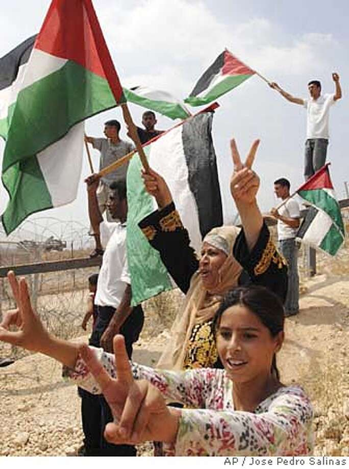 Palestinians hold flags and flash victory signs with their hands as they celebrate the Israeli Supreme Court's resolution to redraw the route of Israel's separation barrier in the West Bank village of Bilin near Ramallah, Tuesday, Sept. 4, 2007. In an embarrassing blow to the Israeli government, the Supreme Court on Tuesday ordered the state to redraw the route of its West Bank separation barrier near a Palestinian village that has come to symbolize opposition to the enclosure. (AP Photo/Jose Pedro Salinas) Photo: JOSE PEDRO SALINAS