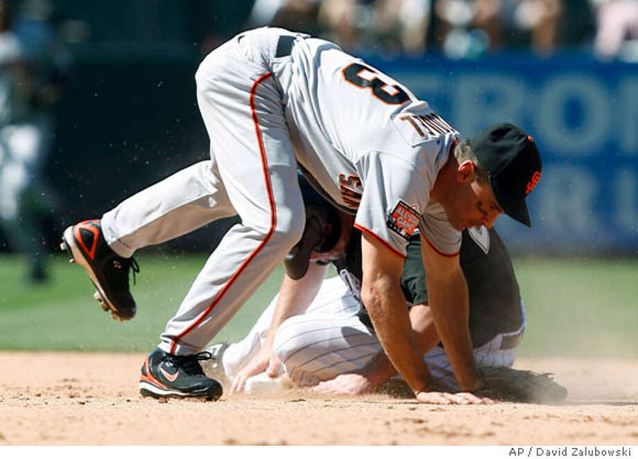 San Francisco Giants shortstop Omar Vizquel, front, hits the ground after forcing out Colorado Rockies' Garrett Atkins at second base on the front end of a double play hit into by Brad Hawpe to end the fifth inning of the Rockies' 7-4 victory in a baseball game in Denver on Monday, Sept. 3, 2007. (AP Photo/David Zalubowski) Photo: David Zalubowski