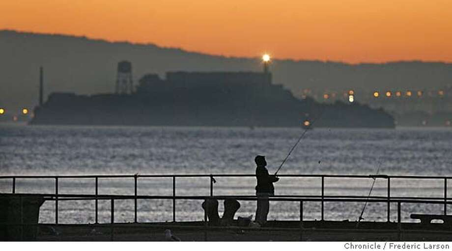 {object name} The early bird gets the fish at Fort Baker pier a fisherman hooks up at dawn and pulls in his prizes. Warm mild weather is in the forecast mostly along the coast. 7:01:01 AM  Model: Canon EOS-1D Mark II N  Frame #: 0644  Lens (mm): 500  ISO: 640  Aperture: 4.0  Shutter: 1/125  Exp. Comp.: -0.7  Program: Shutter Priority 1/25/06  Frederic Larson Photo: Frederic Larson