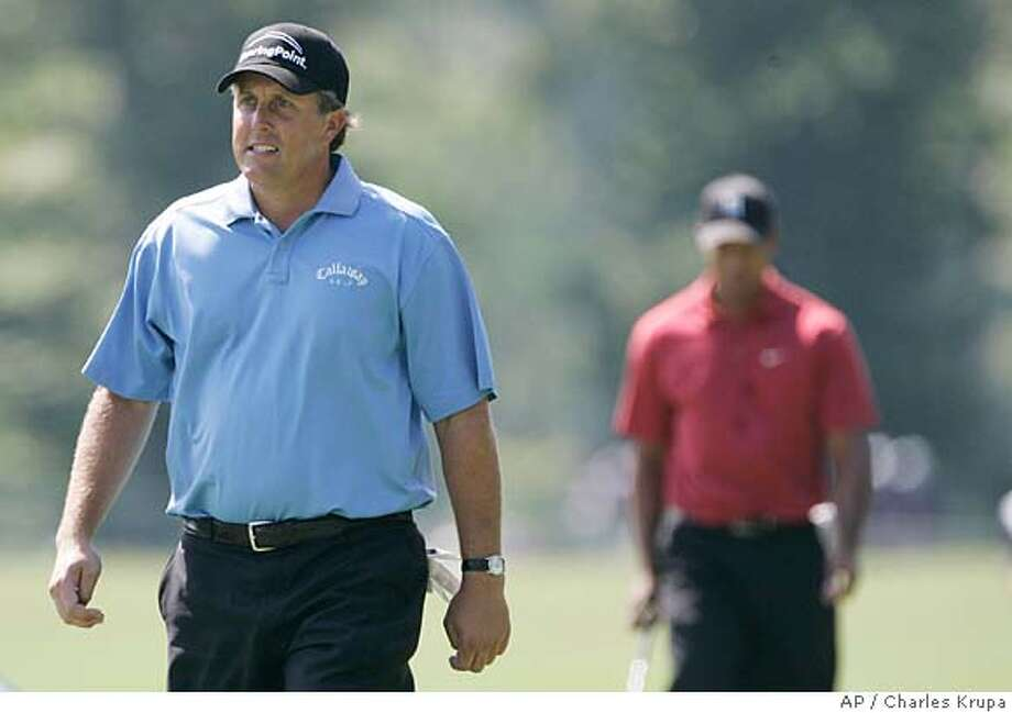 Phil Mickelson, left, walks up the 2nd fairway ahead of Tiger Woods during the final round of the Deutsche Bank Championship golf tournament in Norton, Mass., Monday Sept. 3, 2007. Mickelson won the tournament, beating Woods by two strokes.(AP Photo/Charles Krupa) Photo: Charles Krupa