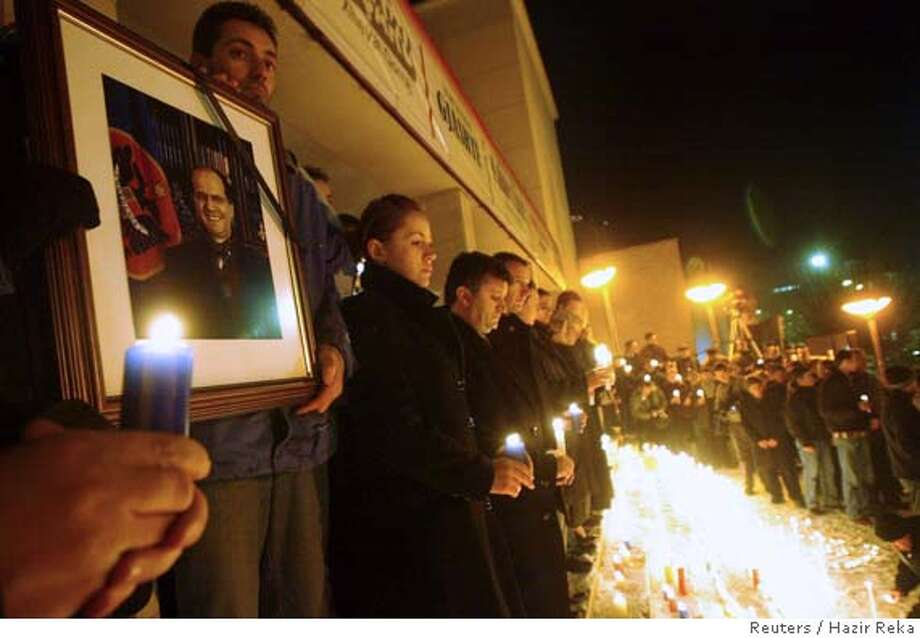 An ethnic Albanian holds a photo of Kosovo President Ibtahim Rugova as Kosovo citizens hold candles in Kosovo's capital Pristina January 21, 2006. Rugova died of lung cancer on Saturday, leaving a leadership vacuum for ethnic Albanians on the eve of talks to secure the independence from Serbia that he championed. A government source in Kosovo said the funeral would take place on Wednesday, the day the United Nations was due to begin direct negotiations between Belgrade and Pristina to decide whether Kosovo's 90-percent ethnic Albanian majority wins independence or remains part of Serbia as Belgrade insists. REUTERS/Hazir Reka Ran on: 01-22-2006  An ethnic Albanian holds a photo of the Kosovo president as citizens mourn his death in the capital of Pristina. Photo: HAZIR REKA