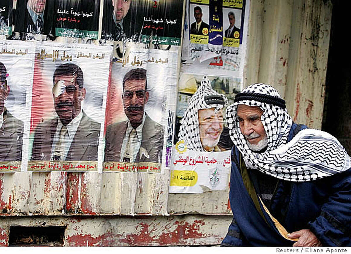 Elderly man walks past wall covered with pre-election posters in Bethlehem
