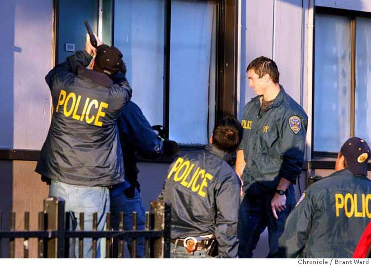 badge_gangtaskforce_282.JPG San Francisco Gang Task Force officers used a battering ram to knock in a door at the housing project while police drew their weapons. At San Francisco's Alemany public housing project, members of the Gang Task Force raided several homes with search warrants hoping to capture parole violators and stem the recent violence occurring in the neighborhood. {By Brant Ward/San Francisco Chronicle}8/29/07