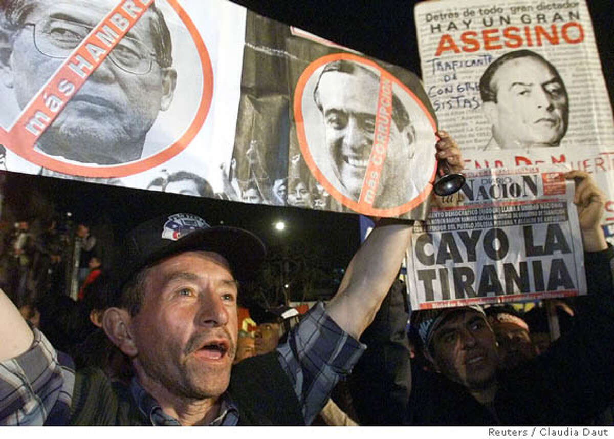 A protester yells slogans while holding pictures of Peruvian President Alberto Fujimori and his long-time adviser Vladimiro Montesinos during a political rally of the opposition at the Plaza San Martin in downtown Lima, September 18, 2000. A scandal erupted last week when a video surfaced showing Vladimiro Montesinos, who has been the power behind President Alberto Fujimori for the last ten years, allegedly bribing an opposition congressman to switch sides. The ensuing scandal prompted Fujimori, who was elected in a tainted ballot in May, to call out for new elections and to assure that he did not plan to run again. Fujimori did not give a timetable for the new poll. REUTERS/Claudia Daut CAT