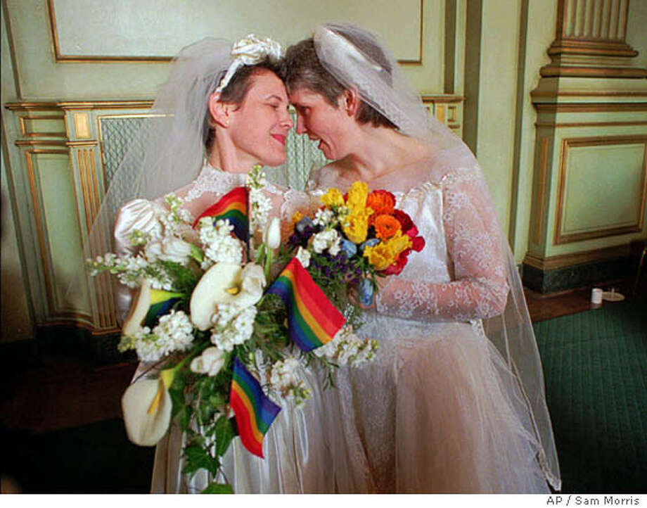 "FILE--Jan Stafford, right, and Maxine Kincora, both wear wedding dresses before they were ""married"" in San Francisco Monday morning, March 25, 1996, under a new San Francisco ordinance. Although same-sex marriages are not legal in the state, dozens of gay and lesbian couples were united in a symbolic union. Many members of the gay and lesbian community feel betrayed by President Bill Clinton's decision to sign a GOP-sponsored bill that would bar federal benefits to same-sex couples even if a state legalized their union. (AP Photo/Sam Morris) Photo: SAM MORRIS"
