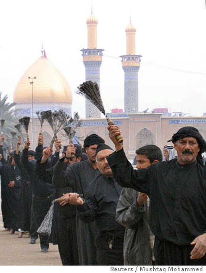 Iraqi residents hold chains for flogging during a procession near the al-Abbas shrine in Kerbala Photo: STRINGER/IRAQ