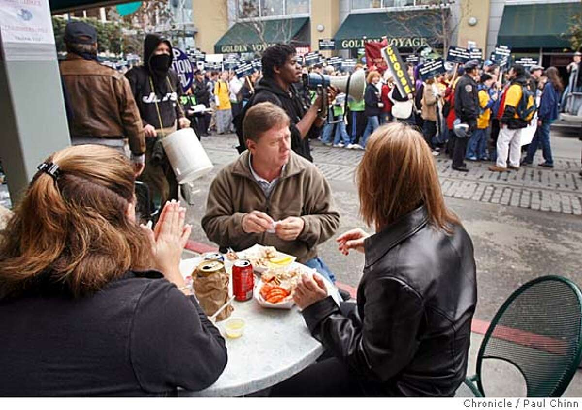 Tourists (who declined to give their names) lunching on crab at Fishermans Wharf paused to watch the second annual Walk For Life anti-abortion march in San Francisco, Calif. on 1/21/06. PAUL CHINN/The Chronicle