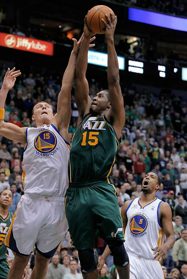 Utah Jazz forward Derrick Favors (15) is fouled by Golden State Warriors center Andris Biedrins (15), of Latvia, as he goes to the basket during the second half of an NBA basketball game in Salt Lake City, Saturday, March 17, 2012. The Jazz defeated the Warriors in overtime, 99-92. (AP Photo/Steve C. Wilson) Photo: Steve C. Wilson, Associated Press