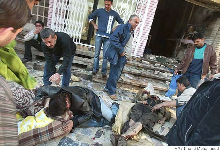 ** GRAPHIC CONTENT ** Friends and relatives grieve over the bodies of two victims from a suicide bomber's attack at the entrance of a coffee shop, Thursday, Jan. 19, 2006, in Baghdad, Iraq. Early reports say that two suicide bombers detonated two explosions, one from a belt and one from the roadside, that left over 25 dead and 25 injured. (AP Photo/Khalid Mohammed) GRAPHIC CONTENT Photo: KHALID MOHAMMED