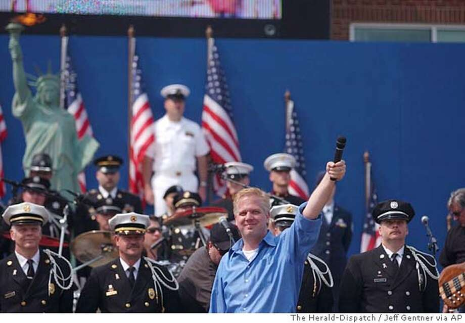 "Radio personality Glenn Beck, center, gets the crowd going, Saturday, May 24, 2003, during the ""Rally for America"" at Marshall Stadium in Huntington, W.Va. The rally was broadcast live to U.S. troops around the world through the Armed Forces Radio Network. Dave Wellman, a Marshall University spokesman, put the estimate at more than 20,000. (AP Photo/The Herald-Dispatch, Jeff Gentner) Photo: JEFF GENTNER"