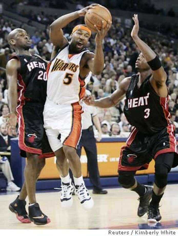 Miami Heat's Dwyane Wade (R) and Gary Payton (L) press Golden State Warriors' Baron Davis as he goes up for a shot in the first half of their NBA game in Oakland, California January 11, 2006. REUTERS/Kimberly White 0 Photo: KIMBERLY WHITE