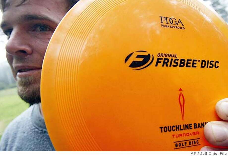 ** FILE ** David Waisblum shows the Original Frisbee Disc Touchline Bank with flight rings made by Wham-O Inc., before playing disc golf at Golden Gate Park in a San Francisco file photo from July 18, 2004. Wham-O Inc., the maker of vintage toys like the Frisbee, Slip'N Slide and Hula Hoop, has been sold to a Hong Kong distributor that's trying to build a one-stop shop for outdoor fun. (AP Photo/Jeff Chiu, File) JULY 18, 2004 FILE PHOTO Photo: JEFF CHIU