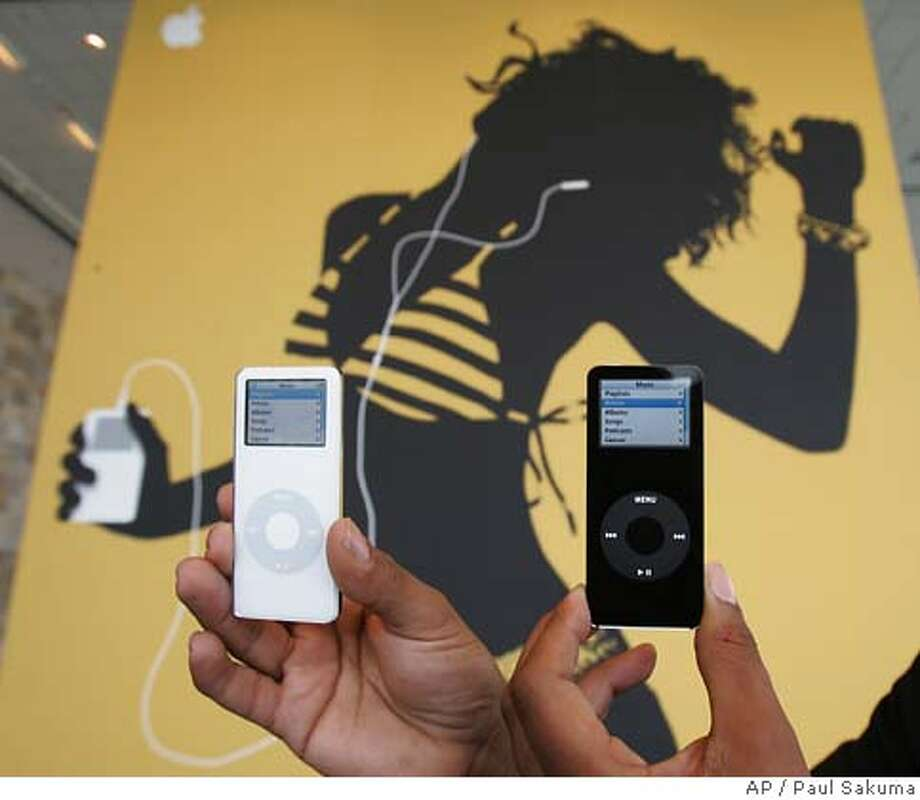 ** FILE **A black and white model of Apple Computers Inc. new iPod Nano on display in front of a giant Apple poster during their announcement in a San Francisco file photo from Sept. 7, 2005. Boosted by strong iPod sales, Apple Computer Inc. is poised to post yet another record-revenue quarter when it reports results after the market close. (AP Photo/Paul Sakuma, File) SEPT. 7, 2005 FILE PHOTO Photo: PAUL SAKUMA