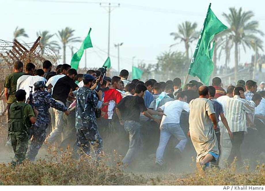 Palestinian members of Hamas' Executive Force prevent Hamas supporters from advancing towards the border crossing with Egypt, during a rally calling for the re-opening of the border in Rafah, southern Gaza Strip, Saturday, Sept. 1, 2007. Eight Palestinian protesters were wounded Saturday, including one pronounced brain dead, at a Hamas rally on the Egyptian border, medics said. (AP Photo/Khalil Hamra) Photo: KHALIL HAMRA