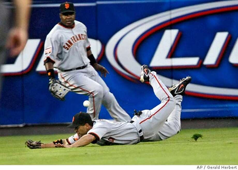 San Francisco Giants center fielder Dave Roberts dives for a base hit by Washington Nationals Ronnie Belliard in the second inning of a baseball game at RFK Stadium in Washington, Saturday, Sept. 1, 2007. Behind him is left fielder Barry Bonds. (AP Photo/Gerald Herbert) Photo: Gerald Herbert
