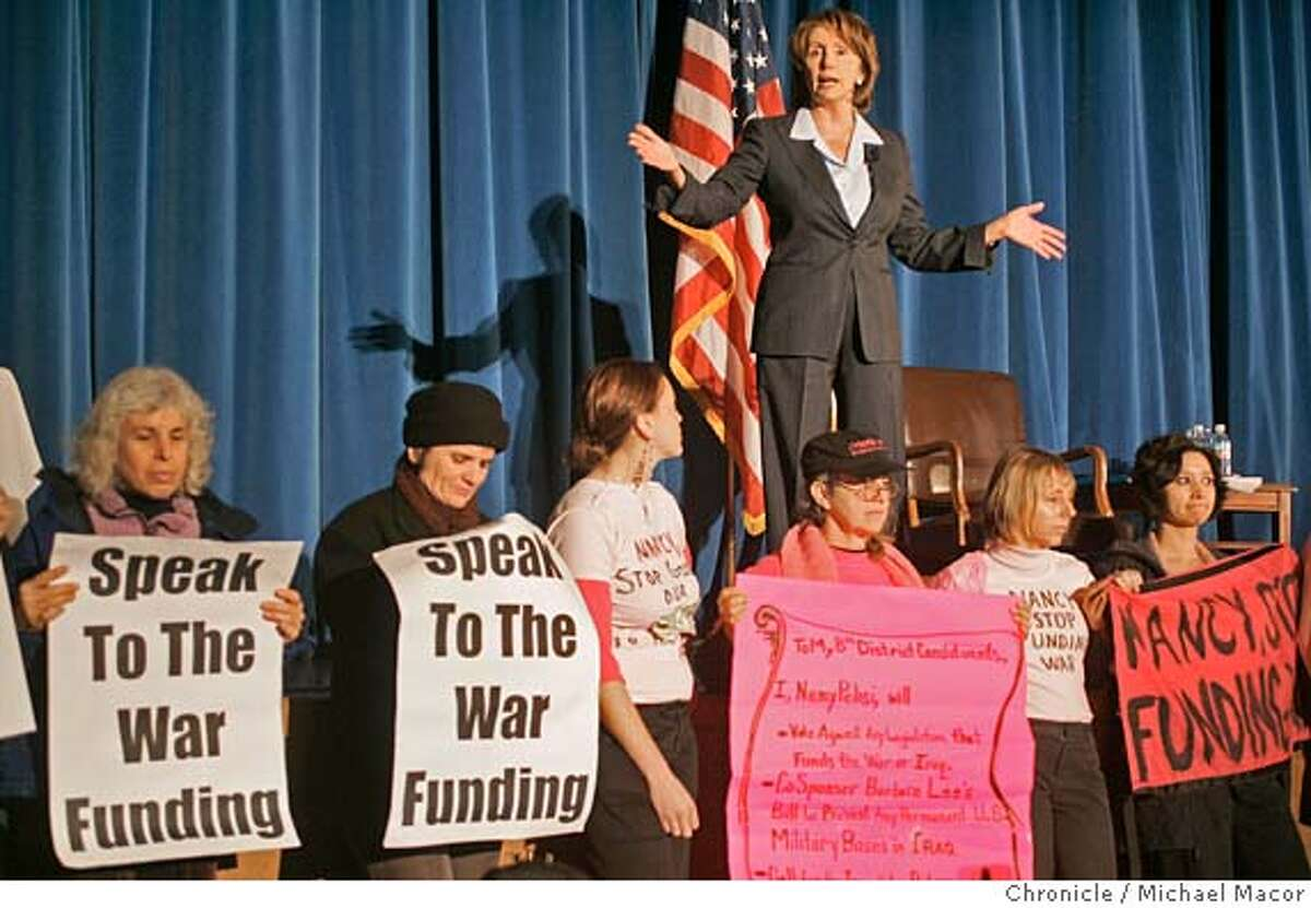 """pelosi_196_mac.jpg Pelosi tries to conduct the Town Hall meeting as protesters lined the front of the stage and stayed there for the entire meeting. Protest groups were from """"Code Pink"""" and """"United for Peace and Justice-Bay Area"""". Congresswoman Nancy Pelosi's Townhall meeting on Iraq and national security is expected to draw 100's of citizens and some protesters, as well. Marina Middle School in the Marina District. Event in San Francisco, Ca on 1/14/06. Photo by: Michael Macor / San Francisco Chronicle Mandatory Credit for Photographer and San Francisco Chronicle/ - Magazine Out"""